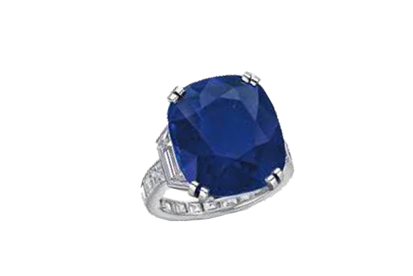 Set with a cushion-cut sapphire, weighing approximately 21.71 carats, flanked on either side by a trapeze-shaped diamond, to the square-cut diamond hoop, mounted in platinum, ring size 6 1/2